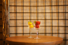 Two beautiful crystal wineglasses full of fruit ice cream. Colorful sorbet with decorative mint on a latticed background. Close-up picture of two portions of Stock Photos
