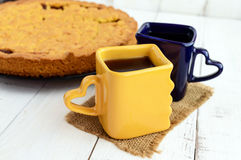 Two beautiful cups (dark blue and yellow) with coffee, tea and freshly baked homemade cake with apricot. Jam stock photo