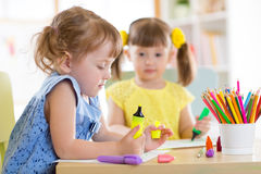 Two beautiful cute kids little girls are drawing at home or daycare centre. Stock Image
