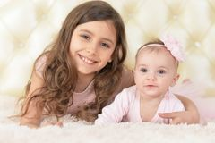 Two beautiful cute sisters. Posing in bed at home Stock Photo