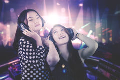 Two beautiful DJ plays music in the nightclub. Photo of two beautiful DJ enjoys their song while playing music in the nightclub Stock Photos
