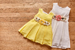 Two beautiful dress for little girls on wooden background. Royalty Free Stock Image