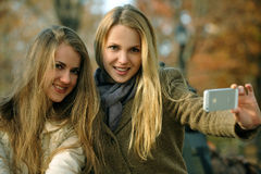 Two beautiful elegant girls shooting themselves Stock Photos