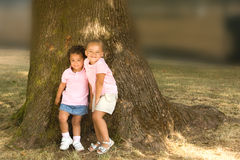 Two beautiful ethnic sisters little girls. In the park posing against the base of a large tree trunk stock photo