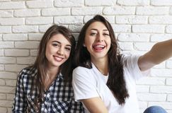Portrait of two millennial females, fooling around in front of mobile smartphone camera. Brown eyed model girls with long brunette. Two beautiful excited young Royalty Free Stock Photo