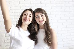 Portrait of two millennial females, fooling around in front of mobile smartphone camera. Brown eyed model girls with long brunette. Two beautiful excited young Stock Photography
