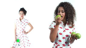 Two beautiful fashion models posing in studio. Black american model and asian model isolated in white background. Fashion shot. Stock Photography