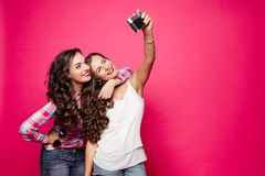 Two beautiful women taking self portrait at camera. Stock Photos