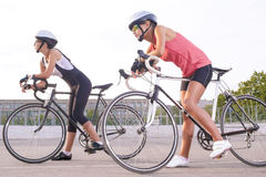 Two beautiful female cyclists taking a break outdoors. Royalty Free Stock Photo