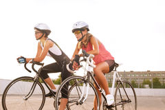 Two beautiful female cyclists taking a break outdoors. Royalty Free Stock Images