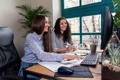 Two beautiful female designers or architects jointly solve work tasks while working in modern office near window. Two smiling female designers or architects royalty free stock images