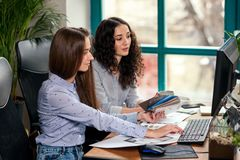 Two beautiful female designers or architects jointly solve work tasks while working in modern office near window. Creative people or advertising business royalty free stock image