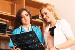 Two beautiful female doctors smile at work Stock Images