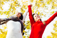 Two beautiful female enjoying in the park on autumn day Stock Photo