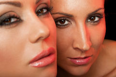 Two beautiful female faces. Close-up of two female faces, looking at camera royalty free stock photos