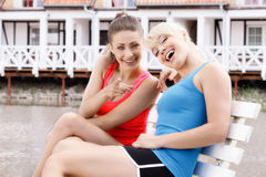 Two beautiful female friends resting on bench. And pointing at camera. Selective focus stock photos