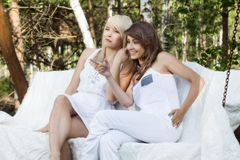 Two beautiful female friends resting on swing and talking. Selective focus royalty free stock photos