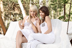Two beautiful female friends resting on swing and talking Royalty Free Stock Image