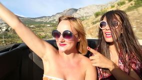 Two beautiful female friends riding in the back seat of convertible stock video