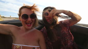 Two beautiful female friends riding in the back seat of convertible stock video footage