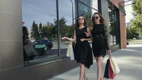 Two beautiful female friends walking after shopping stock video footage