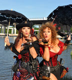 Two beautiful female pirates with parasols blow a kiss Stock Photo