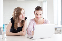 Two beautiful female students working on laptop Stock Photos