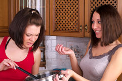 Two beautiful female trying to cook Stock Photography