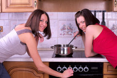 Two beautiful female trying to cook Royalty Free Stock Photography