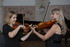 Two beautiful female violinists playing violin stock image