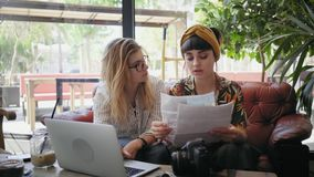 Business presentation and friend talks in cafe shop. Two beautiful female young professionals in field of creativity and photography, meet during business stock footage