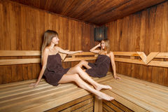 Two beautiful females in sauna. Two beautiful laughing females sitting on the bench and talking in sauna. Wellnes Stock Images