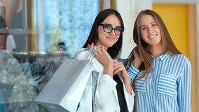 Two beautiful females with shopping bags are looking at camera and smiling while doing shopping in the mall.  stock video