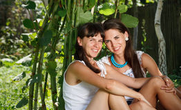 Two beautiful females. Sitting outdoor smiling looking at camera Stock Photo