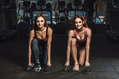 Two beautiful fitness sporty young girls doing lunges with dumbbells in gym stock photography