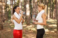 Two beautiful fitness woman drinking water Royalty Free Stock Photography