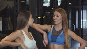 Two beautiful fitness women smiling to the camera at the sports studio. Stunning young red haired sportswoman talking to her beautiful female friend at the gym stock video