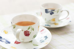 Two beautiful flower pained ceramic cup of tea and hot tea Royalty Free Stock Photo
