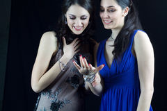 Two beautiful friends admire a ring. Two beautiful friends in elegant dress admire a ring Stock Image