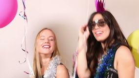 Two beautiful friends having fun dancing in party photo booth. Two beautiful female friends having fun dancing with props in party photo booth stock footage