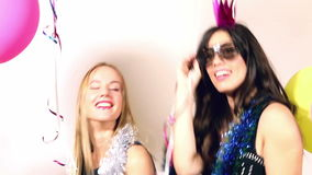 Two beautiful friends having fun dancing in party photo booth. Two beautiful female friends having fun dancing with props in party photo booth, graded stock video