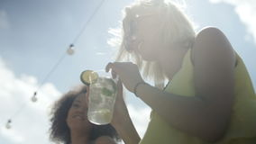 Two beautiful friends having fun during vacation. Close up of woman enjoying tropical mojito cocktail decorated with fresh lemon stock video footage