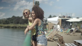 Two beautiful friends having fun during vacation. Beautiful young mixed race girls talking near lake and having great time. Summer/vacation concept stock footage