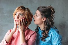 Two beautiful funny young women real friends in casual dress tell each other terrible secrets on concrete wall background. Two beautiful funny young women real stock photography