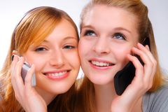 Two beautiful gilrs with mobiles. Two smiling girls with mobile phones Stock Image