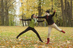 Two beautiful girl friends. In a park jumping Stock Image
