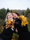 Two beautiful girl friends with autumn leafs. In a park looking up Stock Photo