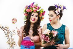 Two beautiful girl friends with candy and flower decoration. sty Stock Image