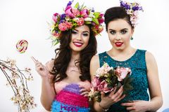 Two beautiful girl friends with candy and flower decoration. sty Stock Photos