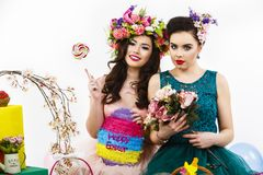 Two beautiful girl friends with candy and flower decoration. sty Royalty Free Stock Photography